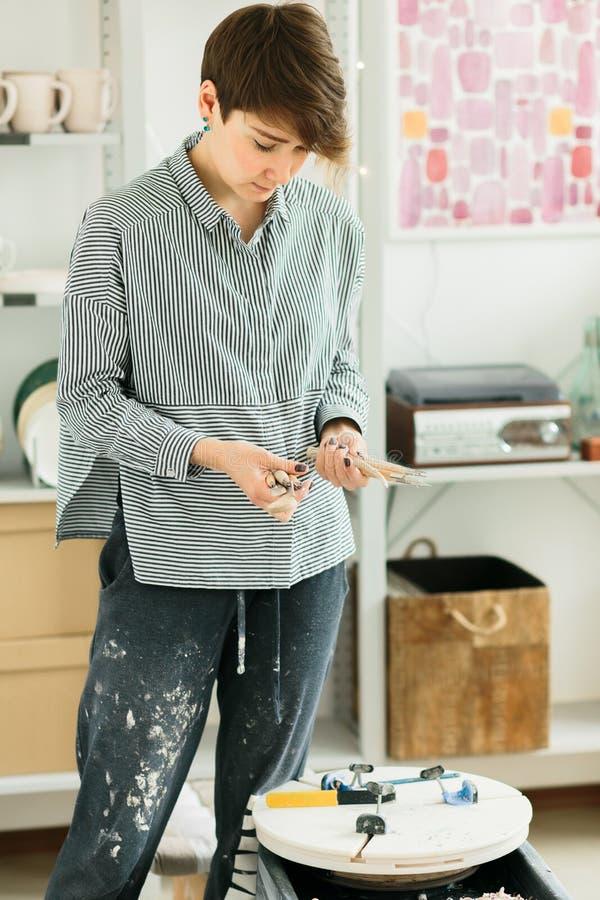Ο αγγειοπλάστης κοριτσιών κρατά τα χαράζοντας εργαλεία στην κεραμική στοκ φωτογραφίες με δικαίωμα ελεύθερης χρήσης