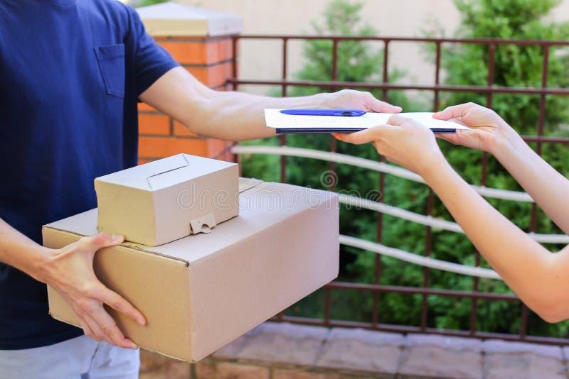 Ο αγγελιαφόρος ατόμων φέρνει τη διαταγή στον πελάτη, δίνει τη μάνδρα και το έγγραφο στα SIG στοκ εικόνα