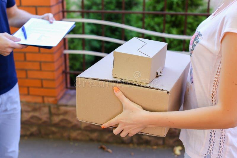 Ο αγγελιαφόρος ατόμων φέρνει τη διαταγή στον πελάτη, δίνει τη μάνδρα και το έγγραφο στα SIG στοκ εικόνες