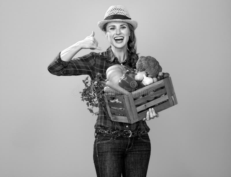 Ο αγρότης γυναικών με το κιβώτιο της παρουσίασης λαχανικών με καλεί χειρονομία στοκ φωτογραφίες