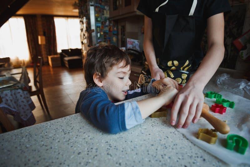 Ο αδελφός δύο αγοριών προετοιμάζει τη ζύμη για τα μπισκότα Ο αριθμός του παλαιότερου αγοριού δεν είναι πλήρως ορατός στοκ εικόνα με δικαίωμα ελεύθερης χρήσης