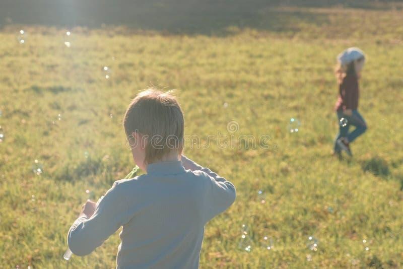 Ο αδελφός και η αδελφή κάνουν τις φυσαλίδες σαπουνιών σε ένα λιβάδι και παίζουν σε μια θερμή ημέρα άνοιξη στοκ εικόνα με δικαίωμα ελεύθερης χρήσης