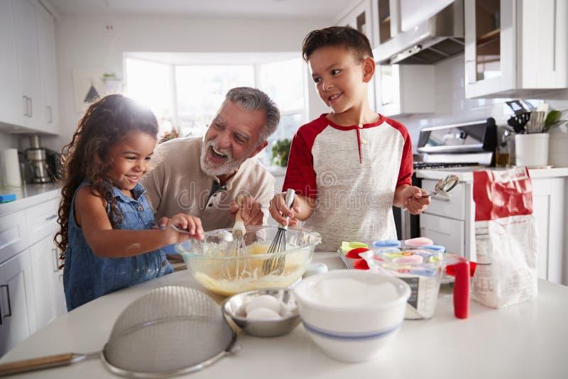 Ο αδελφός και η αδελφή που στέκονται στον πίνακα κουζινών που κατασκευάζει το κέικ να αναμίξει με τον παππού τους, κλείνουν επάνω στοκ εικόνες με δικαίωμα ελεύθερης χρήσης