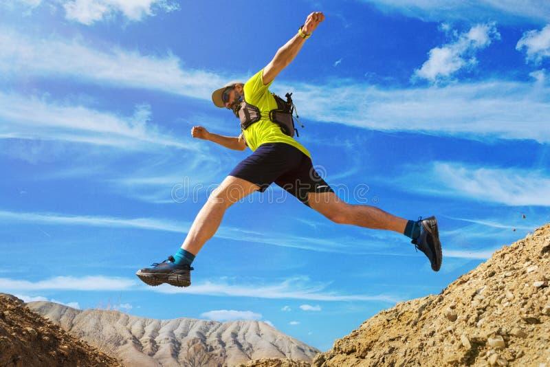 Ο αθλητής τρέχει πλαϊνό Άλματα πέρα από ένα φαράγγι Δρομέας ιχνών στην έρημο στοκ φωτογραφία