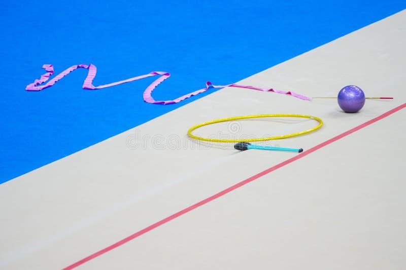 Ο αθλητικός εξοπλισμός για τη ρυθμική γυμναστική βρίσκεται στην άκρη του τάπητα στη γυμναστική Ρυθμικές λέσχες γυμναστικής, μια σ στοκ εικόνες με δικαίωμα ελεύθερης χρήσης