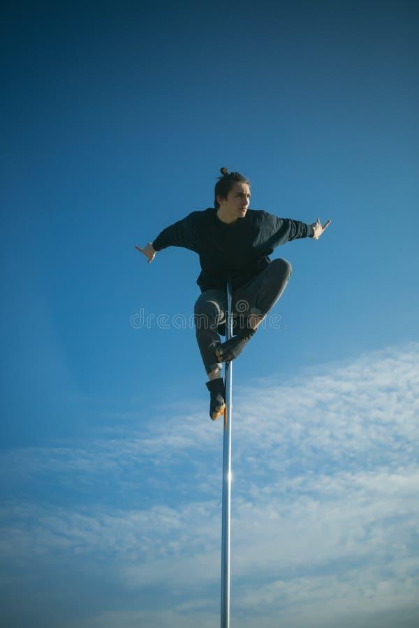 Ο αθλητικός τύπος κάνει τα ακροβατικά στοιχεία στον πυλώνα Προκλητική μύγα ατόμων φαλλοκρατών στο υπόβαθρο μπλε ουρανού Νεαρός άν στοκ φωτογραφία με δικαίωμα ελεύθερης χρήσης