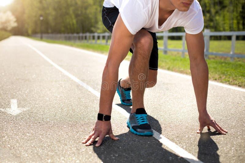 Ο αθλητικός τύπος με τον ιχνηλάτη παίρνει έτοιμος να τρέξει υπαίθρια στοκ εικόνες με δικαίωμα ελεύθερης χρήσης