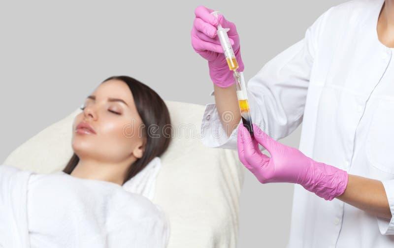 Ο αισθητηριολόγος κάνει θεραπεία στο πρόσωπο μιας όμορφης γυναίκας σε ένα σαλόνι ομορφιάς Υπάρχει πλάσμα αίματος in vitro, έτοιμο στοκ εικόνα με δικαίωμα ελεύθερης χρήσης