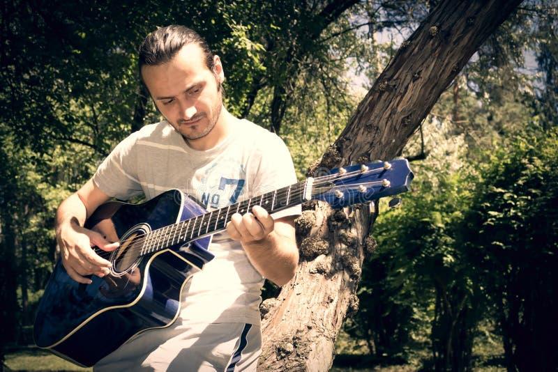 ο ακουστικός κιθαρίστας κιθάρων λεπτομερειών δίνει το instrumant μουσικό παιχνίδι φορέων εκτελεστών στοκ φωτογραφίες