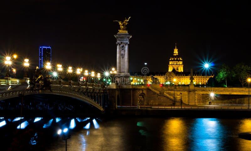 Ο Αλέξανδρος ΙΙΙ γέφυρα και ο θόλος του Invalides τη νύχτα στοκ εικόνα