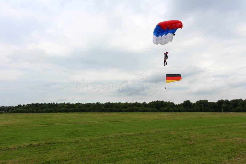 Ο αλεξιπτωτιστής προσγειώνεται με τη γερμανική σημαία στοκ εικόνα