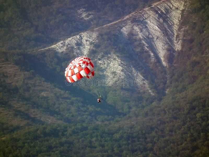 Ο αλεξιπτωτιστής σε ένα κόκκινο και άσπρο αλεξίπτωτο κατεβαίνει ενάντια στο σκηνικό των δασικών βουνών στοκ εικόνα
