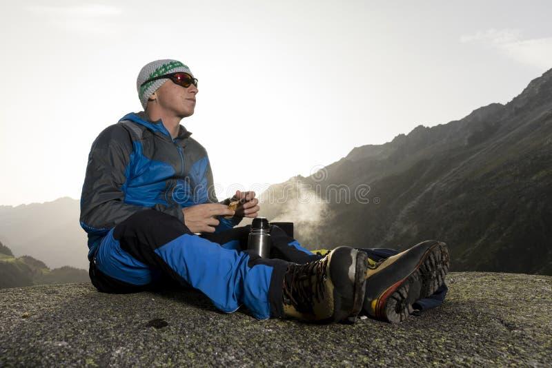 Ο αλπινιστής σταματά και προετοιμάζει ένα θερμό ποτό, Ελβετία στοκ εικόνα