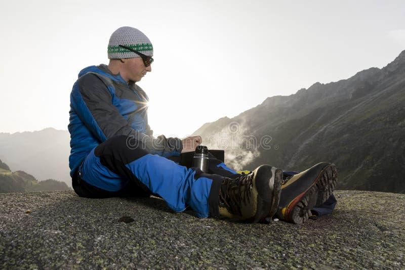 Ο αλπινιστής σταματά και προετοιμάζει ένα θερμό ποτό, Ελβετία στοκ εικόνα με δικαίωμα ελεύθερης χρήσης