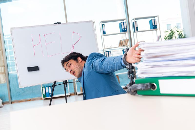 Ο αλυσοδεμένος άνδρας υπάλληλος δυστυχισμένος με την υπερβολική εργασία στοκ εικόνες