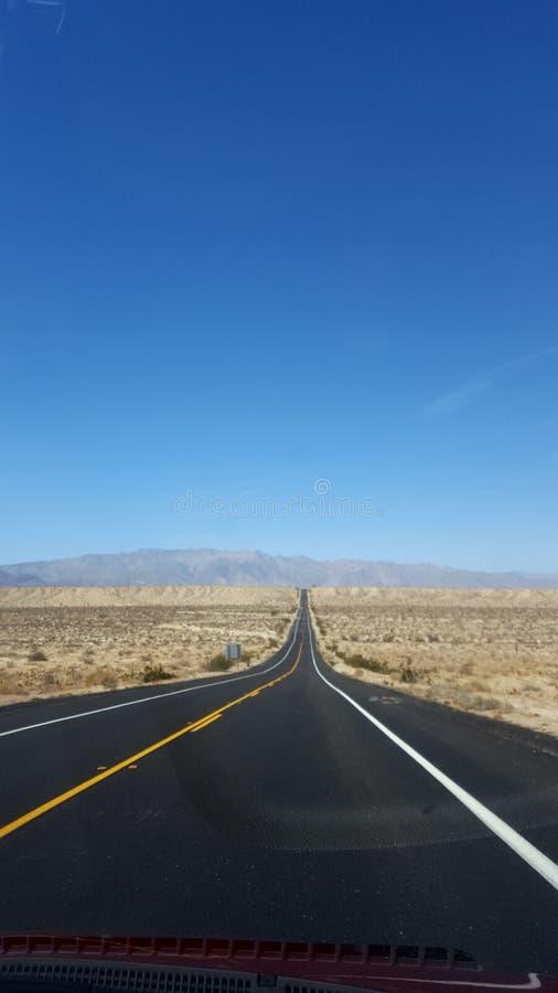 Ο αμερικανικός δρόμος πηγαίνει μπροστινός μπλε ουρανός στοκ εικόνες
