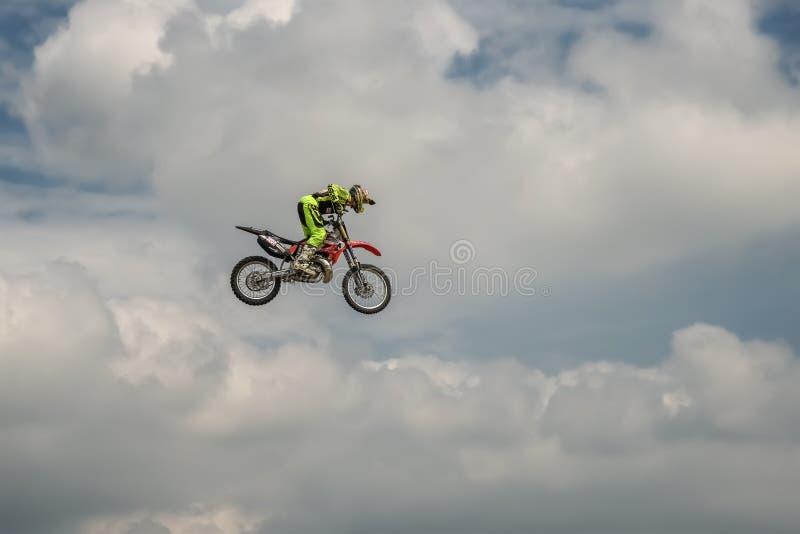 Ο αναβάτης μοτοκρός ελεύθερης κολύμβησης πραγματοποιεί ένα τέχνασμα με τη μοτοσικλέτα στο υπόβαθρο του μπλε ουρανού σύννεφων Πέτα στοκ φωτογραφίες με δικαίωμα ελεύθερης χρήσης