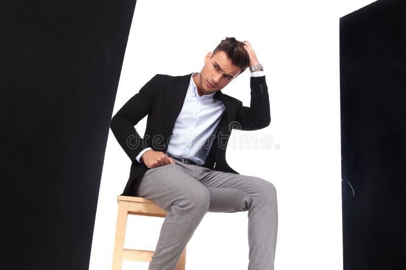 Ο ανησυχημένος επιχειρηματίας κάθεται στην καρέκλα και κοιτάζει κάτω στην πλευρά στοκ φωτογραφίες