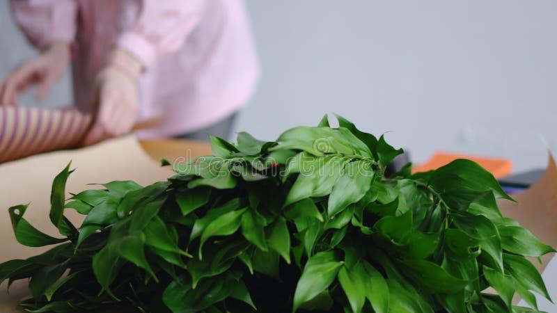 Ο ανθοκόμος προετοιμάζει τα εργαλεία για να δημιουργήσει μια όμορφη ανθοδέσμη Στα πλαίσια της πρασινάδας στοκ εικόνα