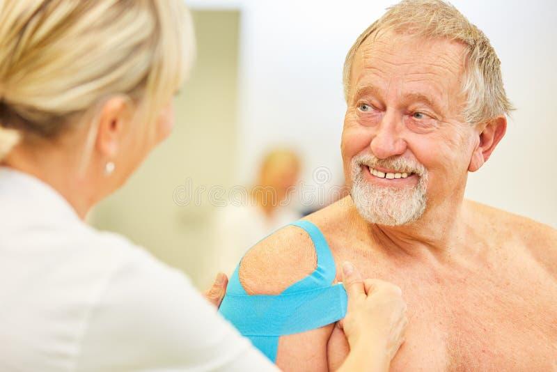Ο ανώτερος ασθενής είναι χαρούμενος για τη λήψη του Kinesio στοκ εικόνα