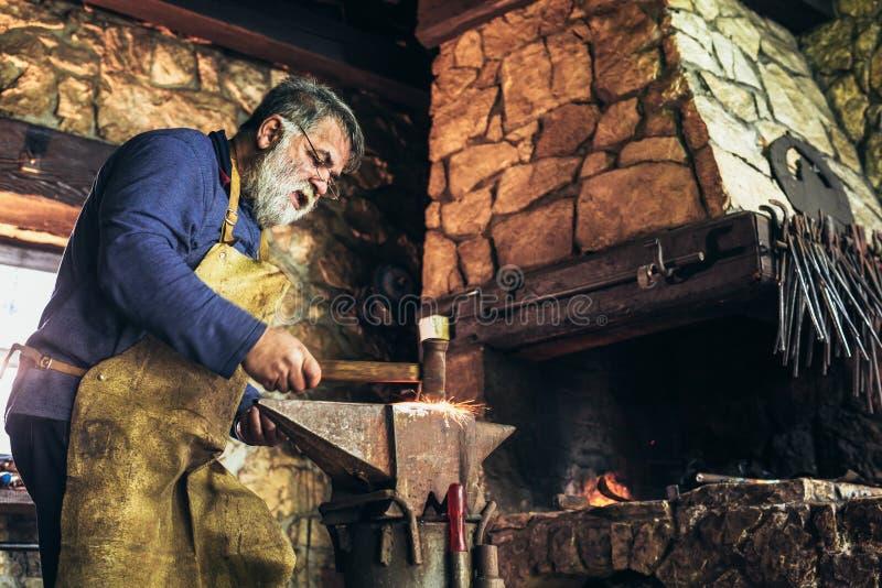 Ο ανώτερος σιδηρουργός σφυρηλατεί το σίδηρο στοκ φωτογραφία με δικαίωμα ελεύθερης χρήσης