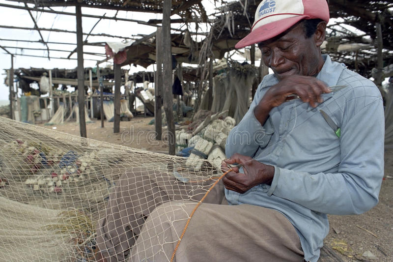 Ο ανώτερος ψαράς κάθεται στο δίχτυ ψαρέματος επισκευής στοκ φωτογραφίες