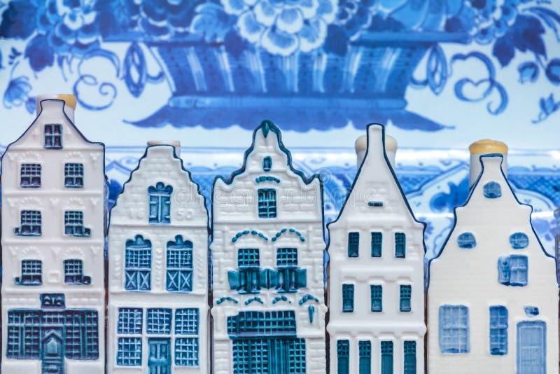 Ολλανδικά σπίτια αναμνηστικών του Ντελφτ μπλε μπροστά από ένα παλαιό πιάτο στοκ εικόνα με δικαίωμα ελεύθερης χρήσης