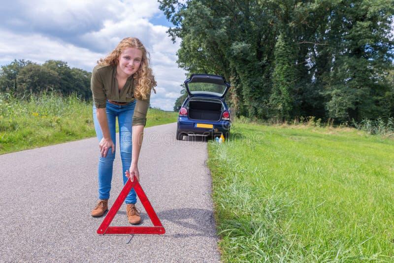 Ολλανδική γυναίκα που τοποθετεί το τρίγωνο προειδοποίησης στον αγροτικό δρόμο στοκ εικόνα