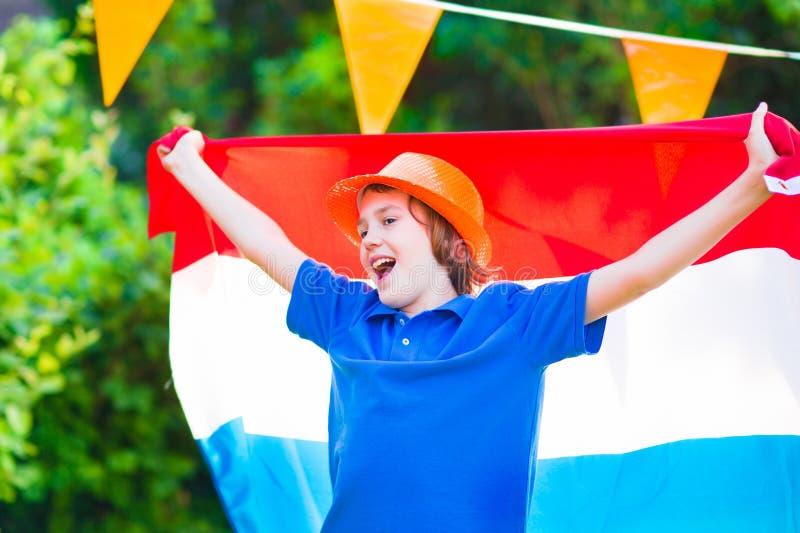 Ολλανδικός οπαδός ποδοσφαίρου, λίγο λατρευτό ευτυχές αγόρι ενθαρρυντικό στοκ φωτογραφία με δικαίωμα ελεύθερης χρήσης