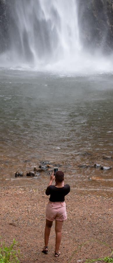 Ο απομονωμένος κολπίσκος πέφτει: γυναίκα που φωτογραφίζει τους δραματικούς καταρράκτες στο φαράγγι ποταμών Blyde, διαδρομή πανορά στοκ φωτογραφίες