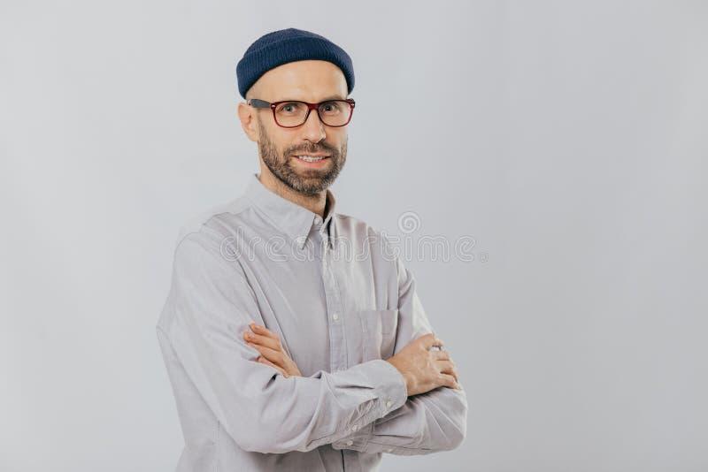 Ο απομονωμένος πυροβολισμός του ευχάριστου κοιτάζοντας αξύριστου αρσενικού κρατά τα χέρια διασχισμένα, φορά το μοντέρνο καπέλο, ο στοκ εικόνες