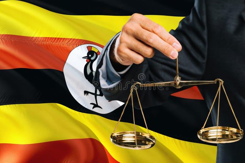 Ο από την Ουγκάντα δικαστής κρατά τις χρυσές κλίμακες της δικαιοσύνης με το κυματίζοντας υπόβαθρο σημαιών της Ουγκάντας Θέμα ισότ στοκ εικόνες με δικαίωμα ελεύθερης χρήσης