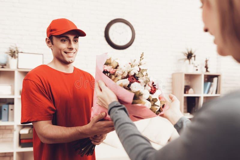Ο αραβικός αγγελιαφόρος στα πορτοκαλιά ενδύματα δίνει το κορίτσι λουλουδιών στοκ εικόνες με δικαίωμα ελεύθερης χρήσης