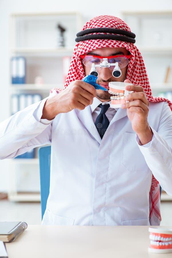 Ο αραβικός οδοντίατρος που εργάζεται στο νέο μόσχευμα δοντιών στοκ φωτογραφία