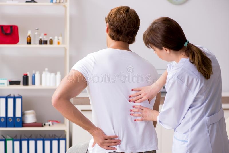 Ο αρσενικός ασθενής που επισκέπτεται το νέο θηλυκό chiropractor γιατρών στοκ φωτογραφία