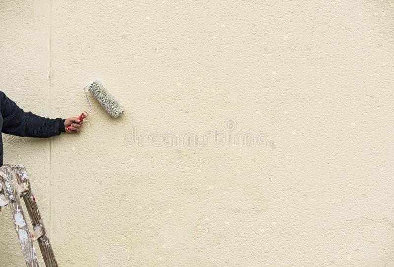 Ο αρσενικός βραχίονας με τον κύλινδρο ζωγράφων στη σκάλα χρωματίζει το λευκό τοίχων στοκ φωτογραφία με δικαίωμα ελεύθερης χρήσης