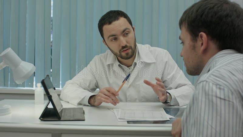 Ο αρσενικός γενειοφόρος γιατρός στην κλινική δίνει τα reccomendations στον πελάτη στοκ φωτογραφία