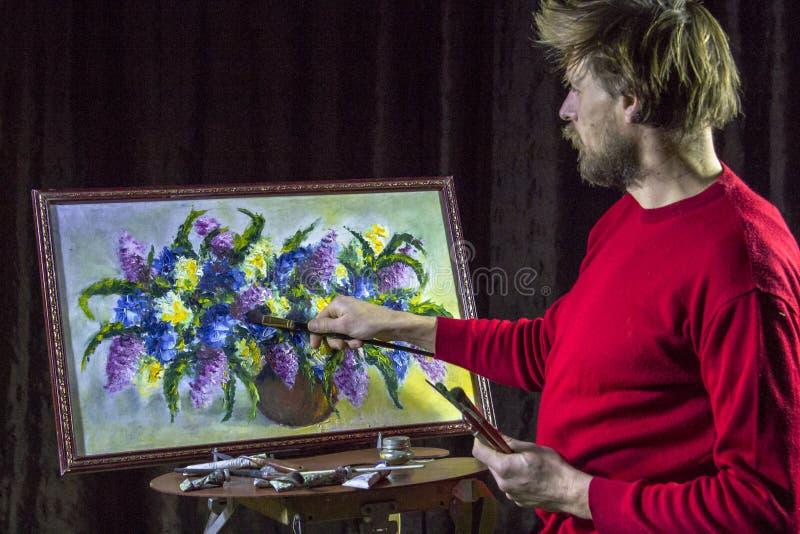 Ο αρσενικός γενειοφόρος καλλιτέχνης σε ένα κόκκινο πουλόβερ σύρει μια καλλιτεχνική ζωή λουλουδιών ζωγραφικής βουρτσών ακόμα στο σ στοκ φωτογραφίες