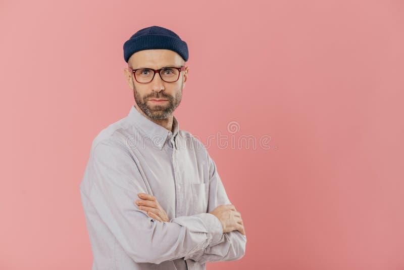 Ο αρσενικός ενήλικος με το παχύ brislte, κρατά τα χέρια διασχισμένα, φορά τα οπτικά γυαλιά, άσπρο επίσημο πουκάμισο, στάσεις λοξά στοκ φωτογραφίες με δικαίωμα ελεύθερης χρήσης
