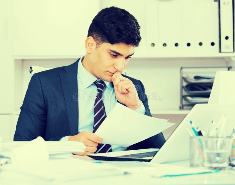 Ο αρσενικός επαγγελματίας διαβάζει τα έγγραφα για τη συναλλαγή στοκ φωτογραφία με δικαίωμα ελεύθερης χρήσης