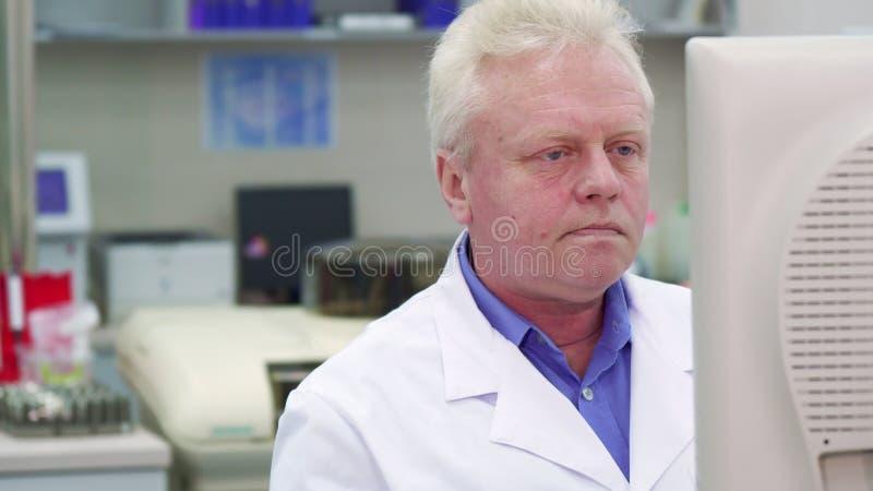 Ο αρσενικός επιστήμονας προσέχει κάποια διαδικασία στο εργαστήριο στοκ φωτογραφίες
