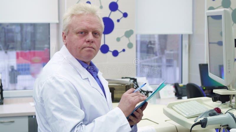 Ο αρσενικός επιστήμονας σημειώνει τις πληροφορίες για την περιοχή αποκομμάτων στο εργαστήριο στοκ φωτογραφίες με δικαίωμα ελεύθερης χρήσης
