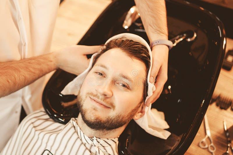 Ο αρσενικός κομμωτής χεριών σκουπίζει το κεφάλι της άσπρης πετσέτας ατόμων μετά από να πλύνει το στοκ εικόνα