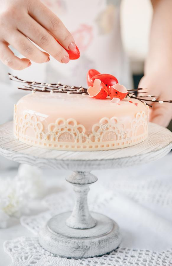 Ο αρσενικός μάγειρας διακοσμεί το κέικ ζύμης με το αυγό σοκολάτας για Πάσχα Ελαφρύ άσπρο γάμμα στοκ εικόνα με δικαίωμα ελεύθερης χρήσης