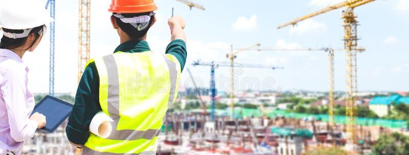 Ο αρσενικός μηχανικός μιλά και σχεδιάζει το κτήριο στο εργοτάξιο οικοδομής στοκ φωτογραφίες