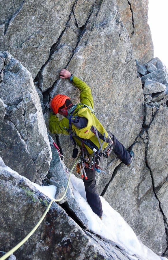 Ο αρσενικός ορειβάτης βουνών διαβαίνει μια δυσνόητη καπνοδόχο βράχου στο δρόμο του σε μια υψηλή αλπική κορυφή στοκ φωτογραφία με δικαίωμα ελεύθερης χρήσης
