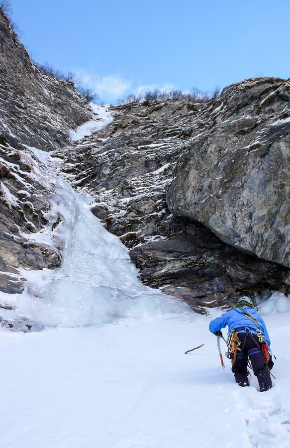 Ο αρσενικός ορειβάτης πάγου πλησιάζει έναν μακρύ και απότομο καταρράκτη σε έναν στενό που παγώνει couloir στις Άλπεις στοκ φωτογραφία με δικαίωμα ελεύθερης χρήσης