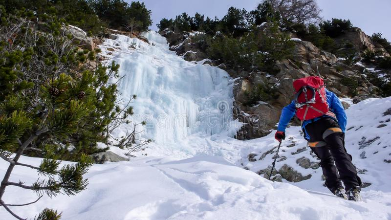 Ο αρσενικός ορειβάτης πάγου σε μια μπλε ζακέτα και ένα κόκκινο σακίδιο πλάτης πλησιάζει μια παγόπτωση μια όμορφη χειμερινή ημέρα  στοκ εικόνα