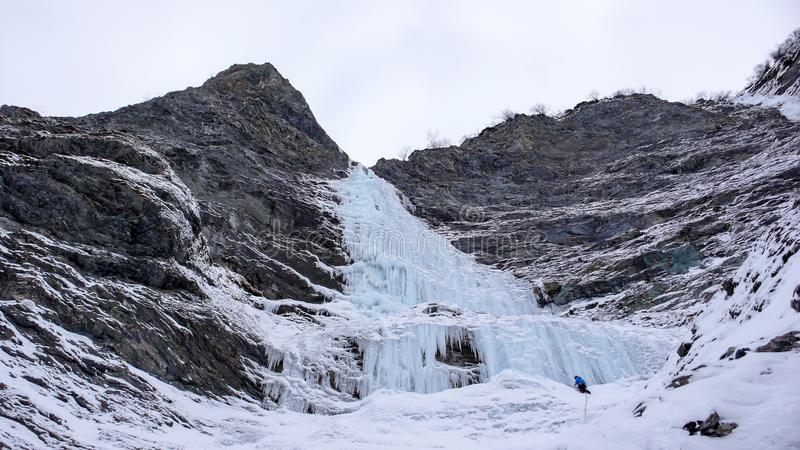 Ο αρσενικός ορειβάτης πάγου στέκεται στο headwall ενός μακριού και απότομου καταρράκτη στις Άλπεις στοκ εικόνα