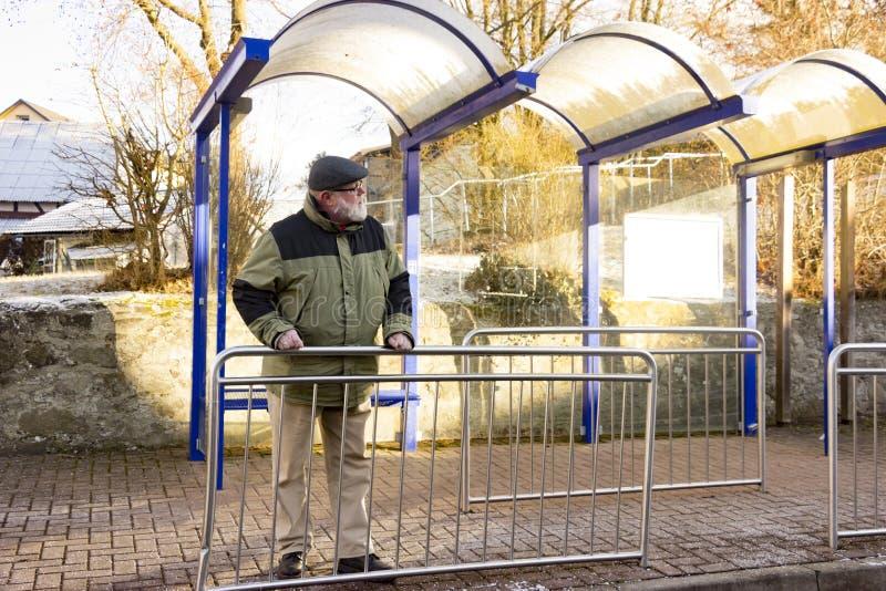 Ο αρσενικός πρεσβύτερος ψάχνει το λεωφορείο στοκ φωτογραφίες